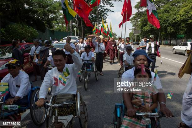 People participating in support of the Myanmar Army carry the Myanmar national flag and flags with the insignia of the army as they march in an...
