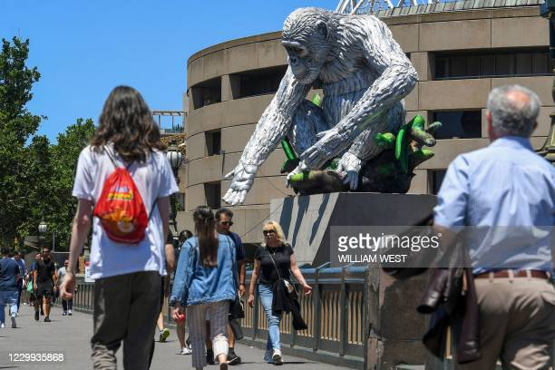People pass a 12-metre tall inflatable sculpture of the chimpanzee David Greybeard by Australian artist Lisa Roet, in Melbourne on December 4, 2020....
