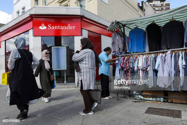 People pass a bank branch of Banco Santander SA near a market in London UK on Tuesday Aug 15 2017 Banco Santander Spains biggest lender has bought...