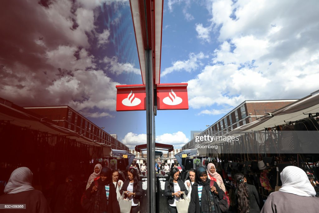 People pass a bank branch of Banco Santander SA near a market in London, U.K., on Tuesday, Aug. 15, 2017. Banco Santander, Spains biggest lender, has bought minority stakes in three financial-technology firms as ChairmanAna Botinmakes machine learning a hallmark of her growth plan. Photographer: Luke MacGregor/Bloomberg via Getty Images