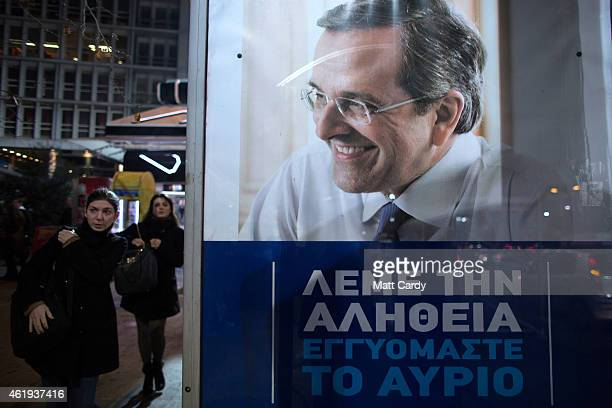 People pass a election poster of Greece's Prime Minister and ruling conservative New Democracy party leader Antonis Samaras ahead of this weekend's...