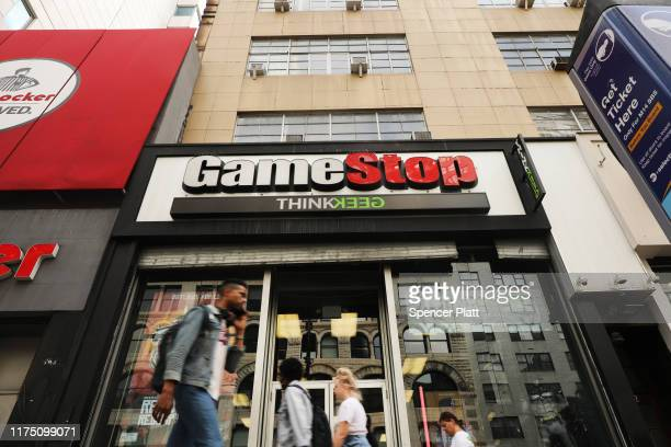 People pass a GameStop store in lower Manhattan on September 16 2019 in New York City GameStop has announced that they will be closing between 180...