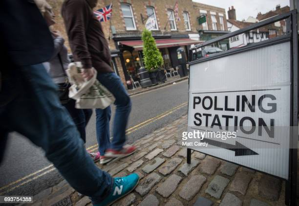 People pass a sign for a polling station in the Council Chamber on June 8 2017 in Eton United Kingdom Polling stations have opened as the nation...