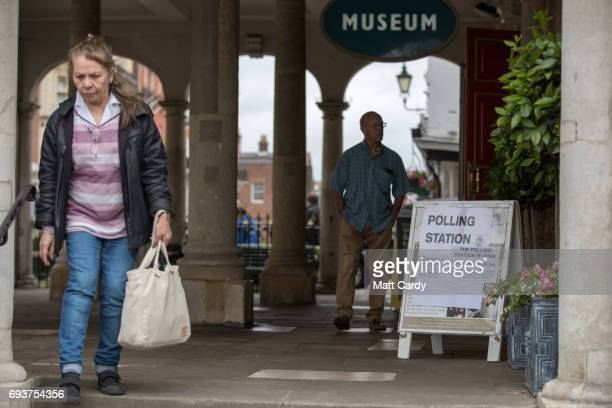 People pass a sign for a polling station in the Windsor Guildhall on June 8 2017 in Windsor United KingdomPolling stations have opened as the nation...