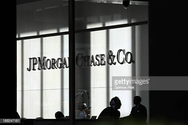 People pass a sign for JPMorgan Chase & Co. At it's headquarters in Manhattan on October 2, 2012 in New York City. New York Attorney General Eric...