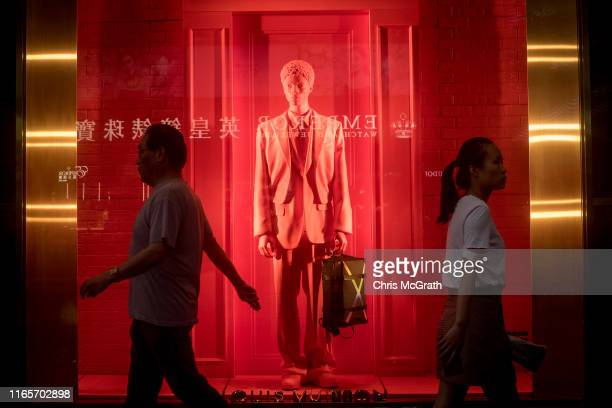 People pass a window display for a luxury brand store on Hong Kong's famous Cant on Road on July 19 2019 in Hong Kong China Hong Kong is approaching...