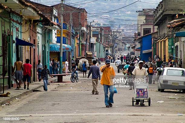 People pass along the main street in the slum of Calvario, Cali, Colombia, 5 April 2004. Calvario, a slum right in the centre of the city, is...
