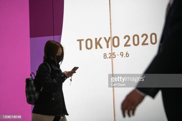 People pass an advert for the Tokyo 2020 Olympics on March 25, 2020 in Tokyo, Japan. Following yesterdays announcement that the Tokyo 2020 Olympics...