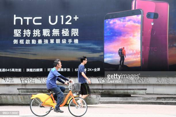 People pass an advertisement for Taiwan smartphone maker HTC in Taipei on July 3 2018 Taiwan's struggling smartphone maker HTC announced on July 3 it...
