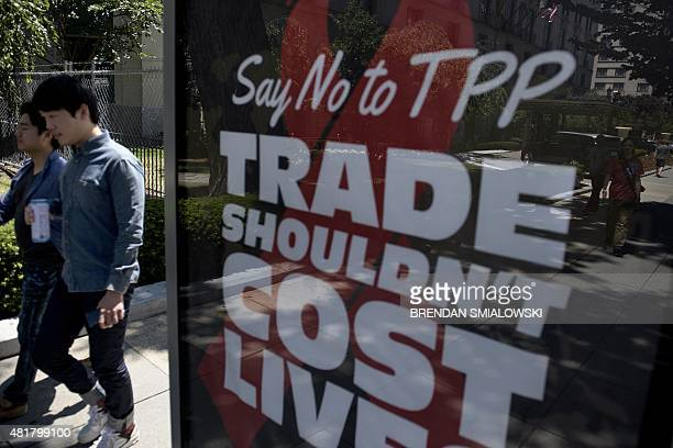 People pass an advertisement protesting the passage of the TransPacific Partnership in Washington DC on July 23 2015 Expectations that the...