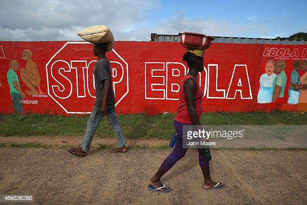 People pass an Ebola awareness mural on October 2 2014 in Monrovia Liberia More than 3200 people have died in West Africa due to the epidemic