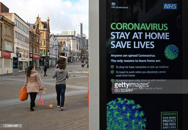 People pass an electronic display board showing British government advice to stay at home and Save Lives as part of national efforts against Covid19...