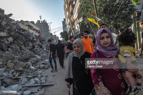 People pass and look at rubble from a previously destroyed building by an air-strike as a ceasefire came into effect on May 21, 2021 in Gaza City,...