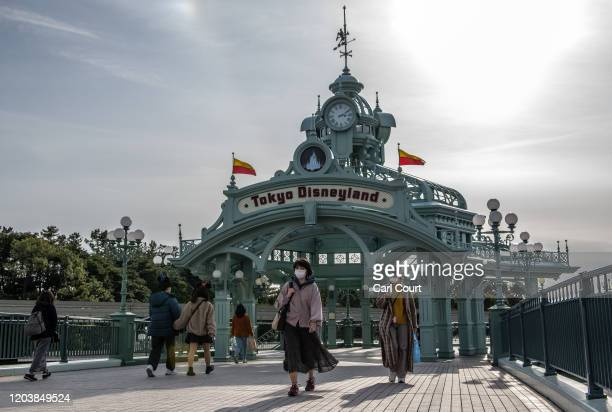 People pass beneath an archway leading to Tokyo Disneyland on the day it announced it will close until March 15th because of concerns over the...