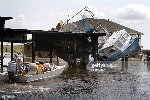 People pass boats knocked out of the water by Hurricane Rita as they head out to check damage to their camps September 26 2005 near Henry Louisiana...
