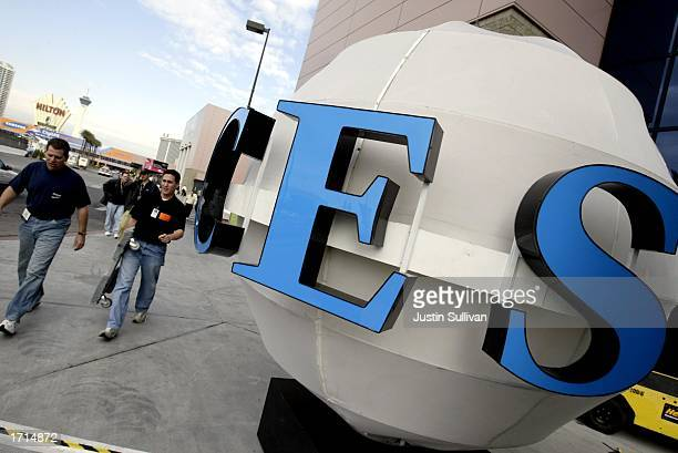 People pass by a CES sign in front of the Las Vegas Convention Center as preparations continue for the 2003 International CES January 8, 2003 in Las...