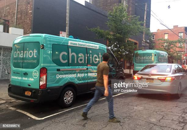People pass by a Chariot commuter shuttle service vehicle on August 2 2017 in New York With its 14seat passenger vans that serve lines created...