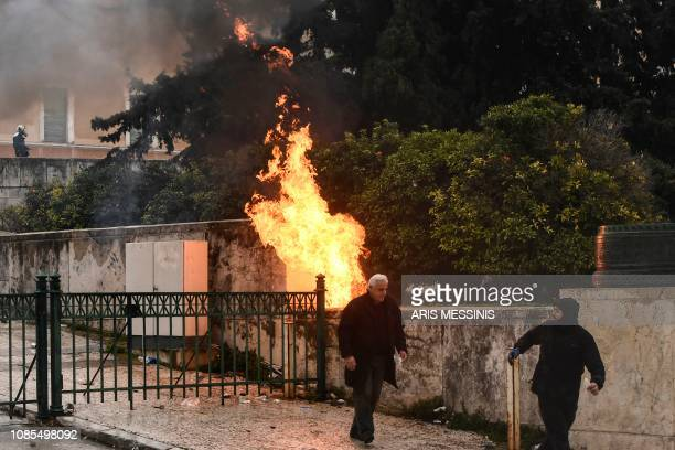 People pass by a fire in front of the Greek Parliament in Athens on January 20 2019 during a demonstration against the agreement with Skopje to...
