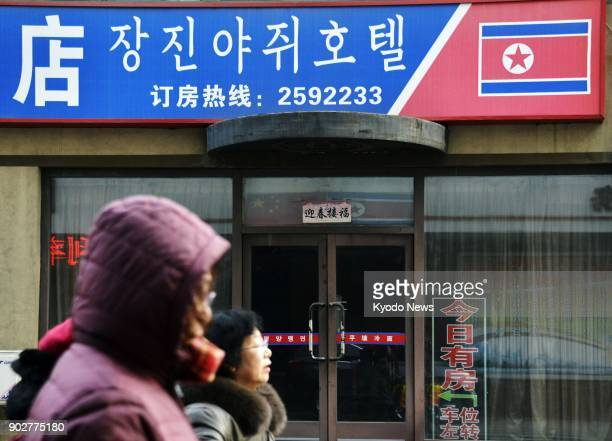 People pass by a hotel where the entrance is locked in Dandong China's border city with North Korea on Jan 7 2018 ==Kyodo