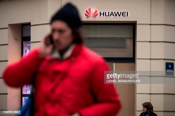 People pass by a Huawei logo above the entrance of a Huawei store in Paris on February 4 2019 A government amendment to establish a preauthorization...