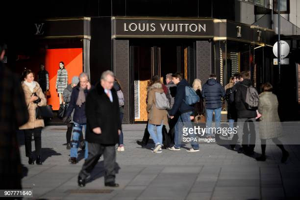 People pass by a Louis Vuitton store in Vienna