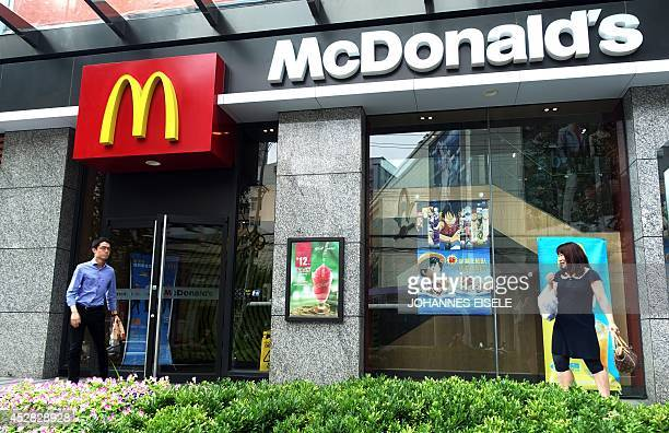 People pass by a McDonald's restaurant on July 28 2014 in Shanghai Some McDonald's restaurants in China have yanked their flagship burgers off the...
