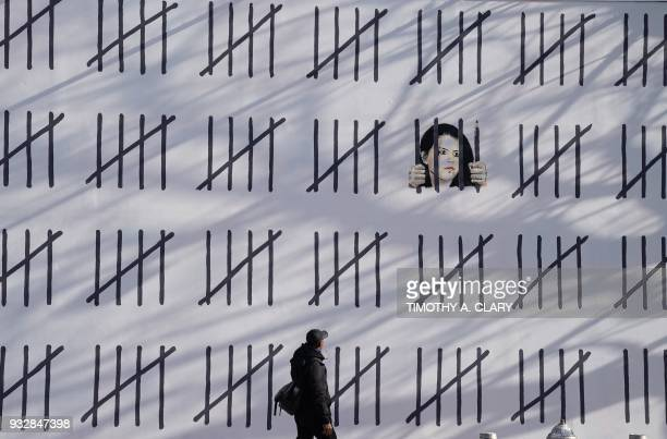People pass by a new 70footlong mural by anonymous British artist Banksy on March 16 2018 that was unveiled on March 15 2018 at the corner of Houston...