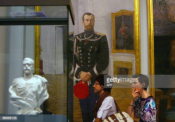 People pass by a painting and a sculpture of late Russian tsar Nicholas II as they visit on July 10 2009 in Monaco the exhibition Moscou Slendeur des...
