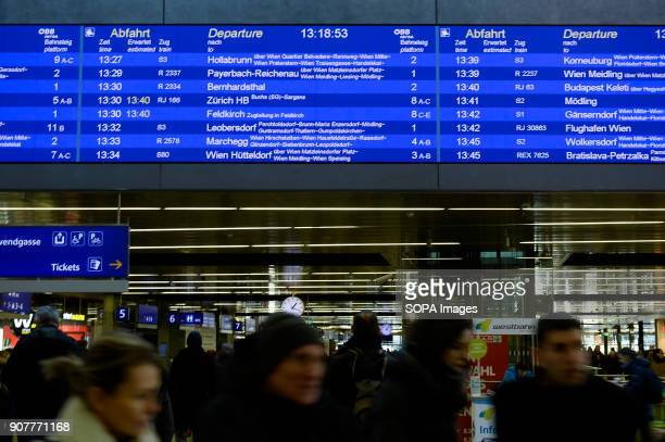 People pass by a schedule panel in Hauptbahnhof railway station in Vienna