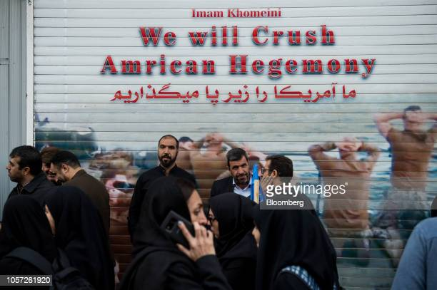 People pass by a shuttered shop displaying the slogan 'We Will Crush American Hegemony' on the anniversary of the U.S. Embassy seizure, in Tehran,...