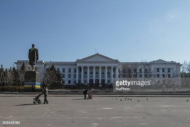 People pass by a statue of Vladimir Lenin draped with a Ukrainian national flag in the eastern city of Kramatorsk Donetsk region President of Ukraine...