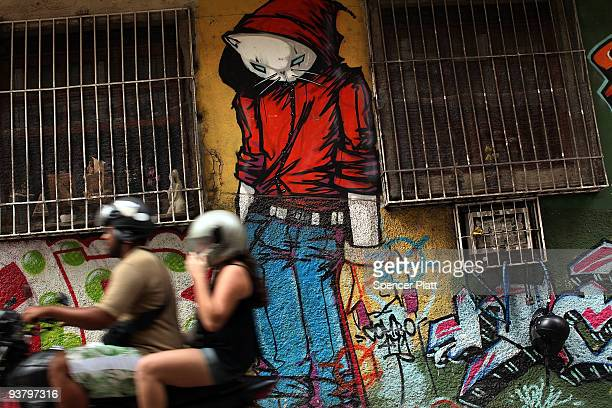"""People pass by a wall with graffiti at the entrance to the recently """"pacified"""" Babilônia slum, or favela, on December 3, 2009 in Rio de Janeiro,..."""