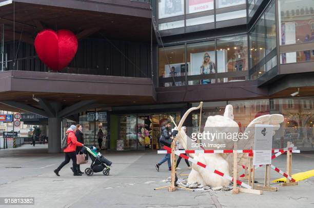 People pass by an art installation with a cupido statue in Prague