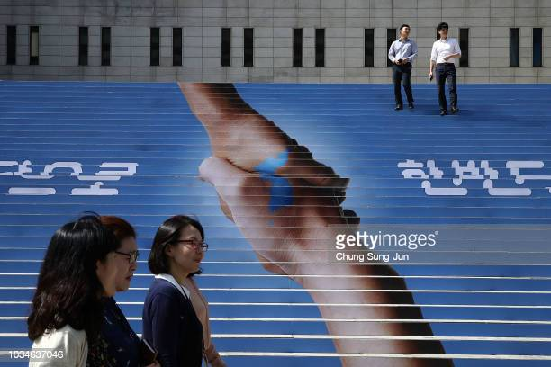People pass by an image of two hands shaking to form the shape of the Korean Peninsula to support the upcoming interKorean summit on September 17...