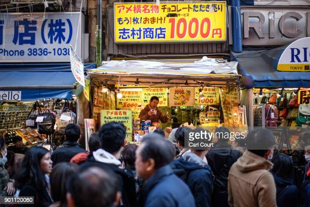 People pass by as a trader sells discount chocolate on a stall in Ameya Yokocho market on January 4 2018 in Tokyo Japan Ameya Yokocho claimed to be...