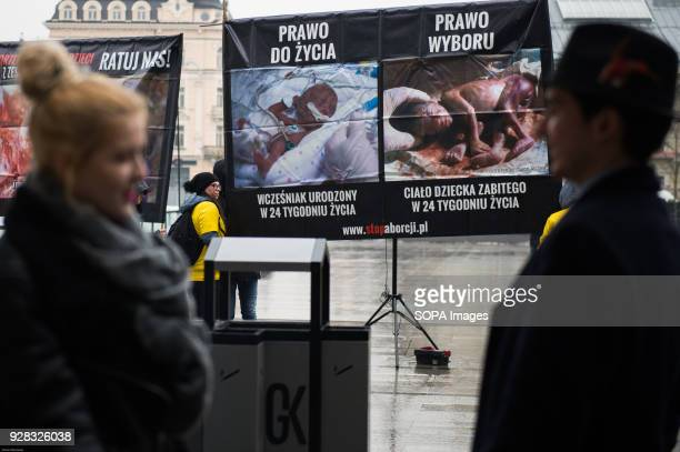 People pass by banners portraying a dead etus during an anti abortion protest organize by 'Foundation Pro' at Galeria Krakowska