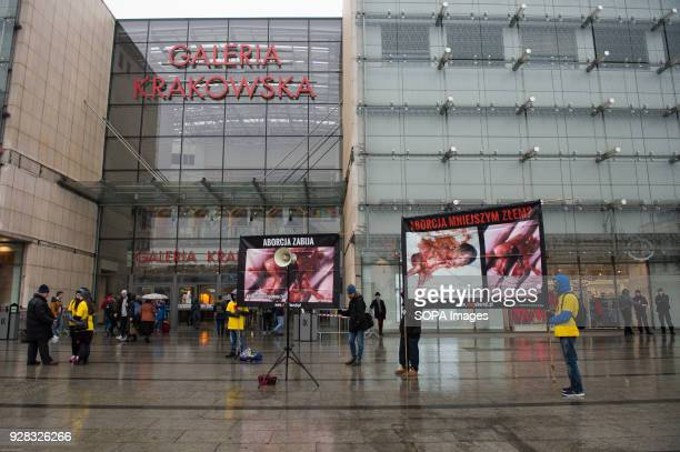 People pass by banners portraying a dead fetus during an anti abortion protest organize by 'Foundation Pro' at Galeria Krakowska