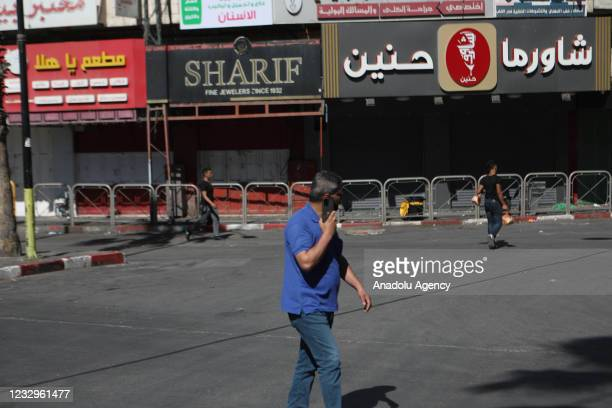 People pass by closed shops as shopkeepers go on a general strike to protest against Israeli attacks over Gaza and East Jerusalem on May 18, 2021 in...