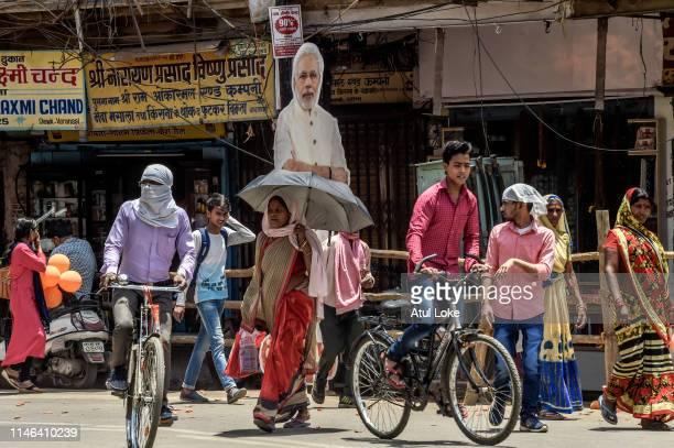People pass by cutout of Narendra Modion May 27, 2019 in Varanasi, India. Naredra Modi prayed at the Kashi Temple in Varanasi after getting nominated...