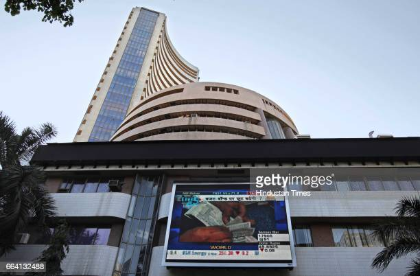 People pass by display screen on BSE building before budgets outside the Bombay Stock Exchange office on Tuesday