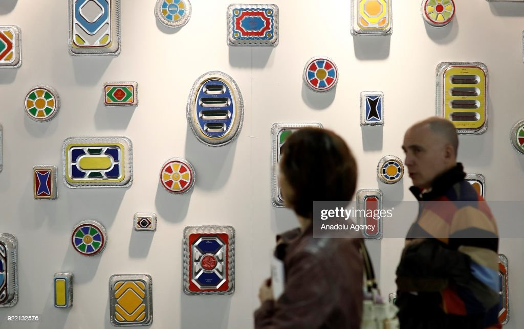 People pass by in front of artworks during ARCOmadrid 2018 in Madrid, Spain on February 21, 2018.