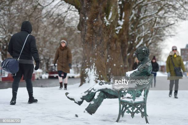 People pass by Patrick Kavanagh's statue near the Grand Canal during a snow shower this afternoon as the 'Beast from the East' has hit Ireland with...