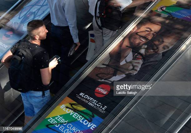 People pass by posters covered with graffiti on an escalator on August 9, 2019 in Budapest, Hungary. The campaign by Coca-Cola promoting gay...