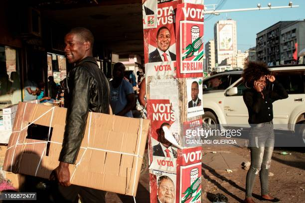 People pass by posters of Mozambican ruling party Mozambican Liberation Front presidential candidate and incumbent President Felipe Nyusi on a...