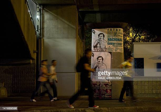 People pass by posters with the image of deceased Colombian drug lord Pablo Escobar along a street of Medellin, Antioquia department, Colombia, on...
