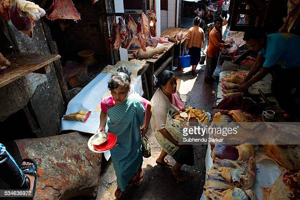 People pass by shops selling beef at Iewduh Bazar in Shillong Meghalaya Lewduh also known as Bara Bazar is a bustling marketplace in Shillong that...