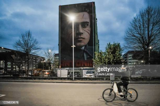 People pass by street artist Jorit's mural of philosopher and politician Antonio Gramsci that paid tribute to football player Diego Armando Maradona...