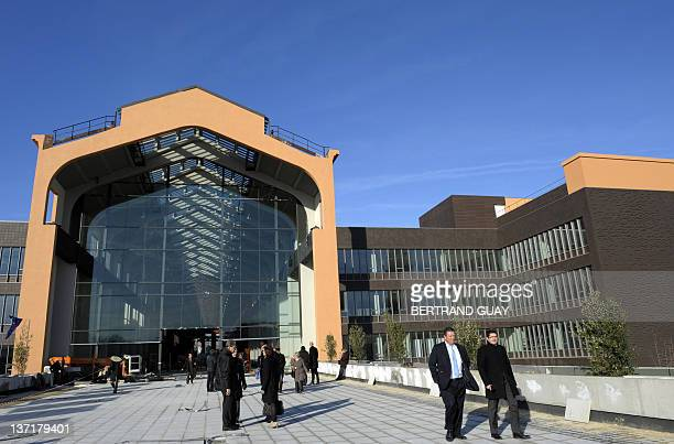 People pass by the front of the Cité du Cinéma as French Prime minister visits it on January 16 2012 in SaintDenis outside Paris The French National...