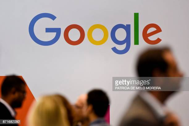 People pass by the Google logo at the Web Summit in Lisbon on November 8 2017 Europe's largest tech event Web Summit will be held at Parque das...