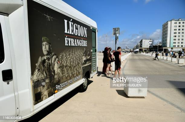 People pass by the Legion's pickup truck on August 7 2019 in BercksurMer during a recruitment campaign for the French Foreign Legion